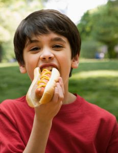 Young boy eating a hot dog